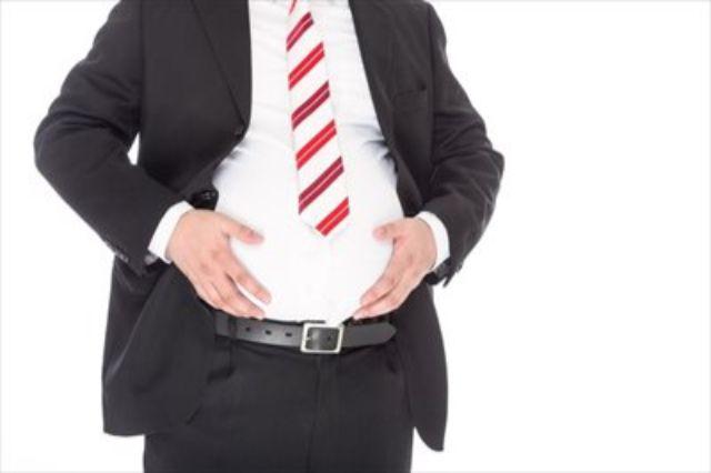 太ったお腹を触るビジネスマン
