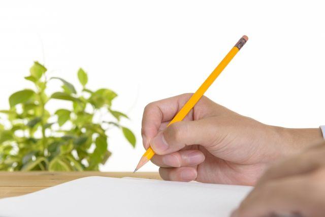 鉛筆でメモを取る人